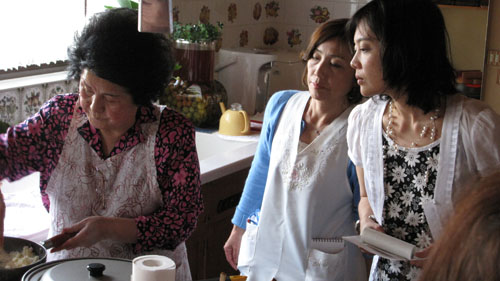 Sachiyo Imai (left) works her magic in the kitchen while an assistant and I take note.